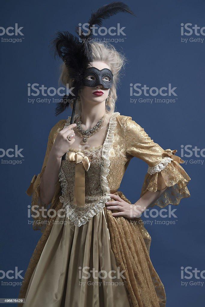 Retro baroque fashion woman wearing gold dress. Holding black mask. stock photo