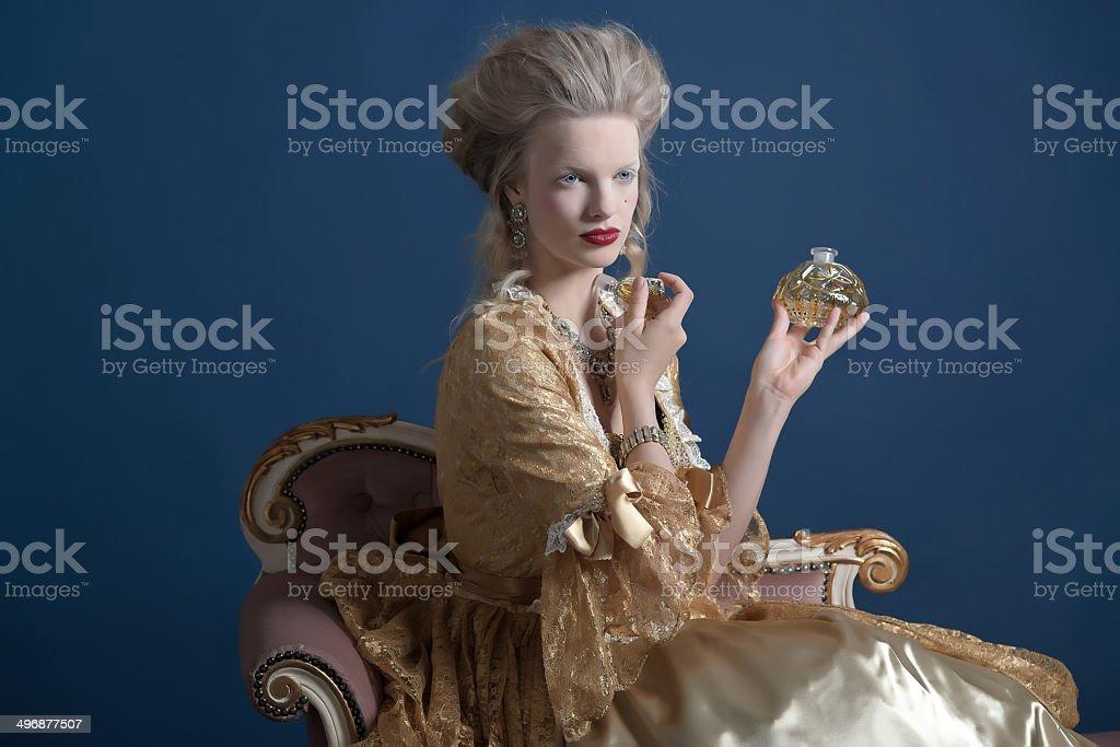 Retro baroque fashion woman wearing gold dress. Holding perfume bottle. stock photo