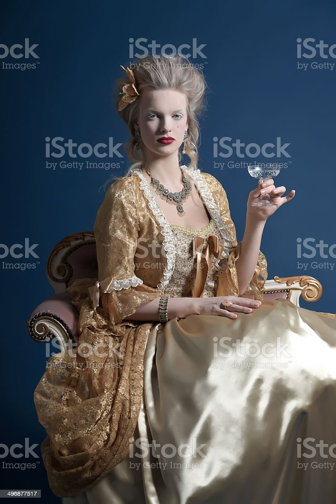 Retro baroque fashion woman wearing gold dress. Holding wine glass. royalty-free stock photo
