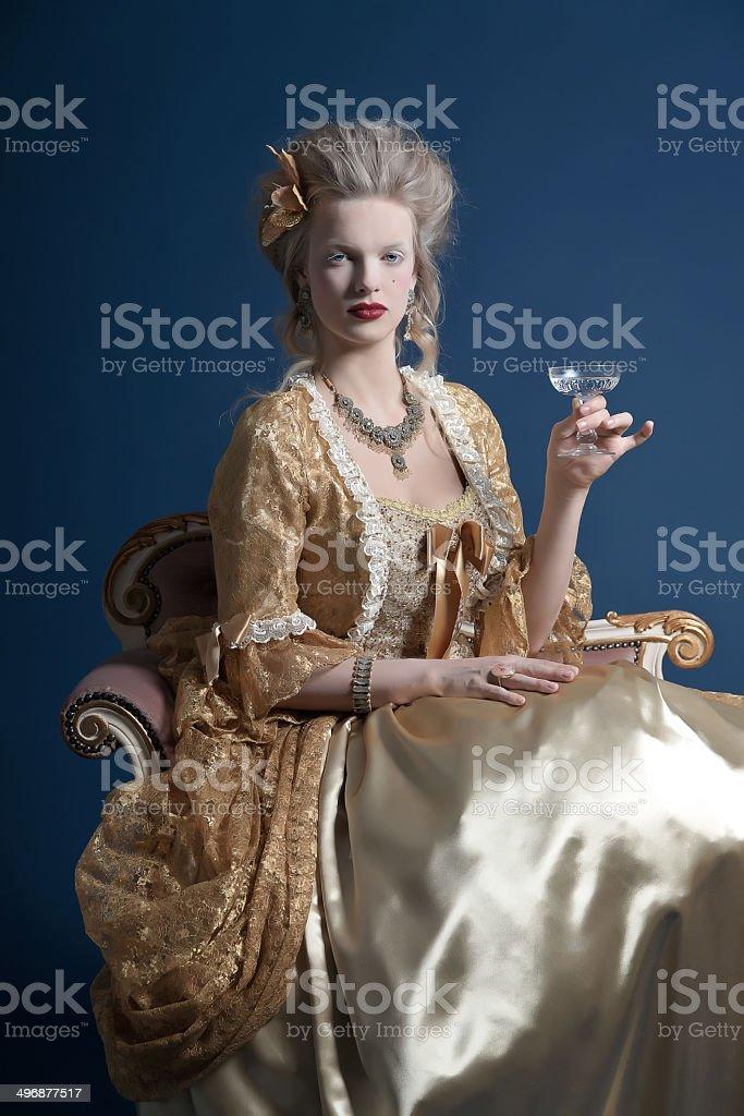 Retro baroque fashion woman wearing gold dress. Holding wine glass. stock photo