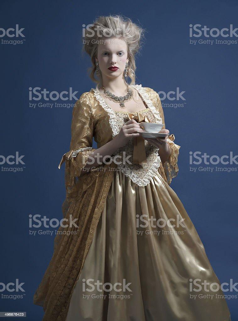 Retro baroque fashion woman wearing gold dress. stock photo