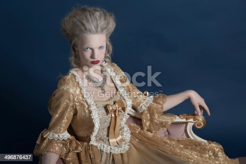 istock Retro baroque fashion woman wearing gold dress. Sitting on couch. 496876437