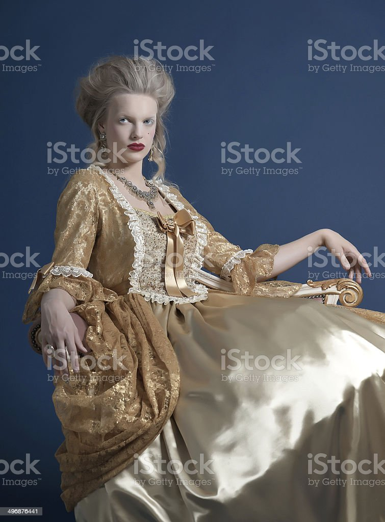 Retro baroque fashion woman wearing gold dress. Sitting on couch. royalty-free stock photo