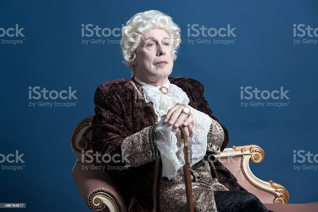 Retro baroque man with white wig holding a walking stick. royalty-free stock photo