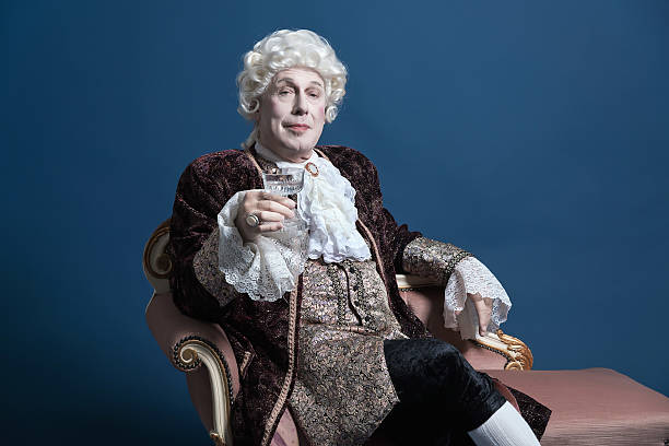 Retro baroque man with white wig holding a wine glass. stock photo