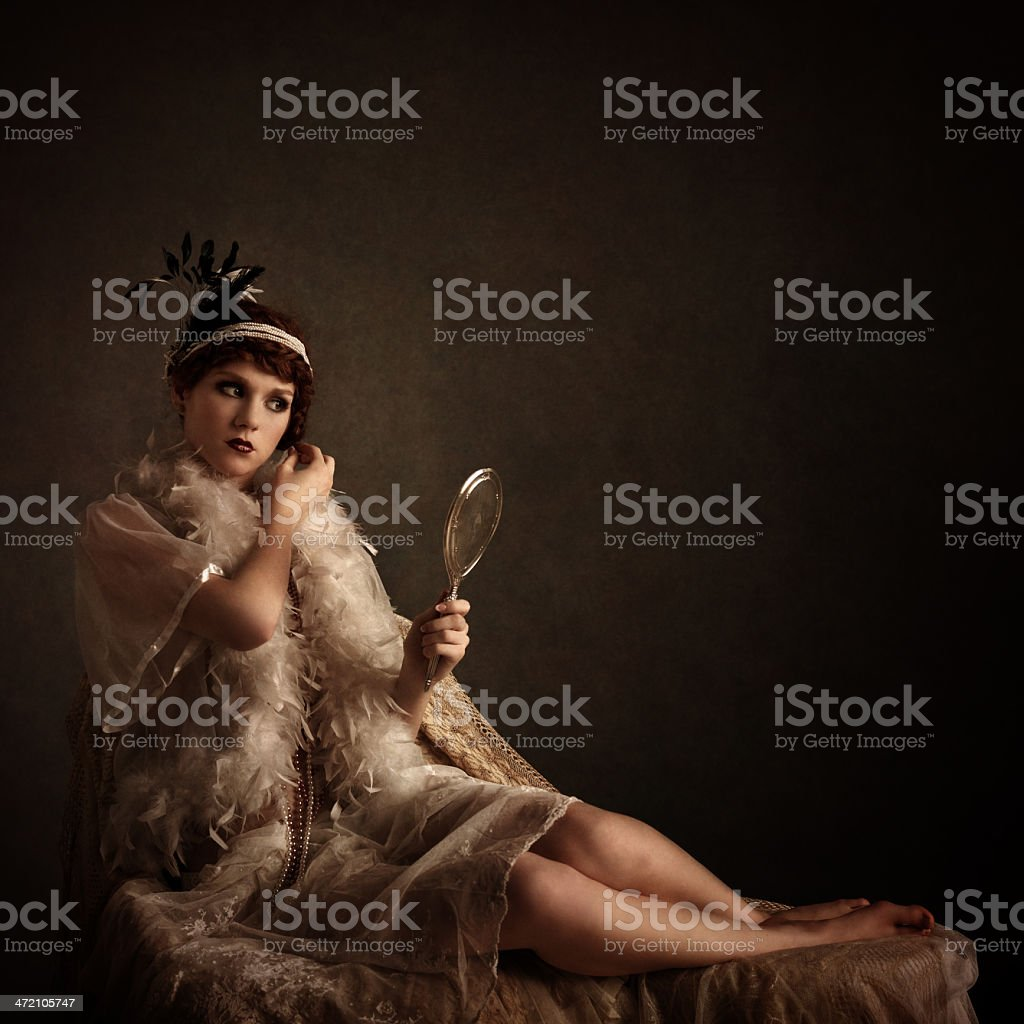 retro beauty looking at herself in a silver hand mirror stock photo