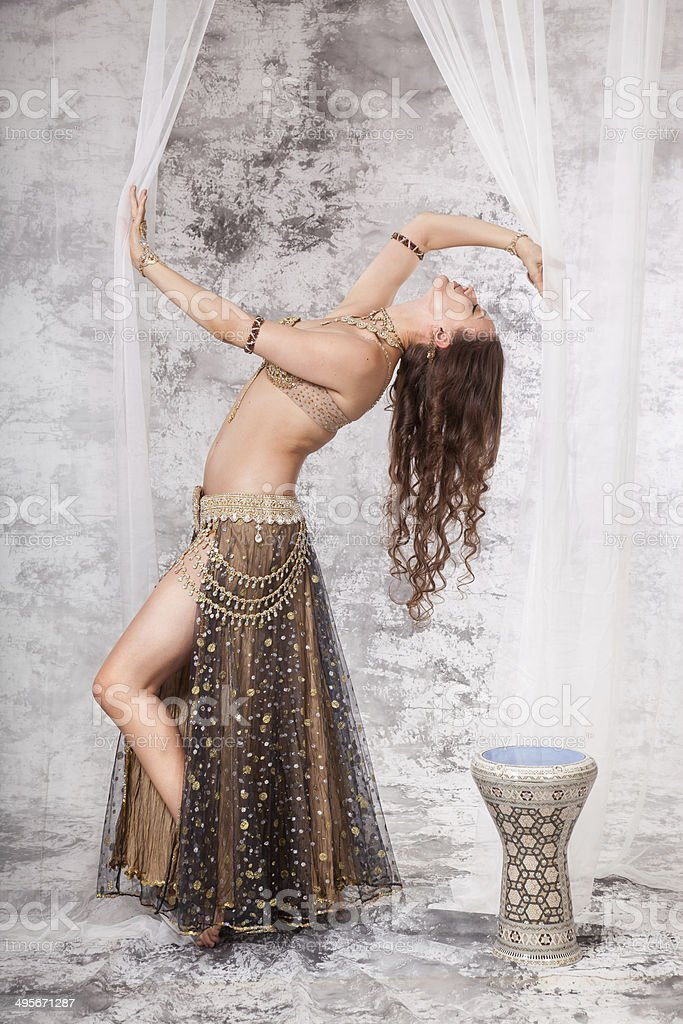 Retro belly dancer in backbend between drapes stock photo