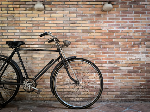 retro bicycle in front of the old brick wall.