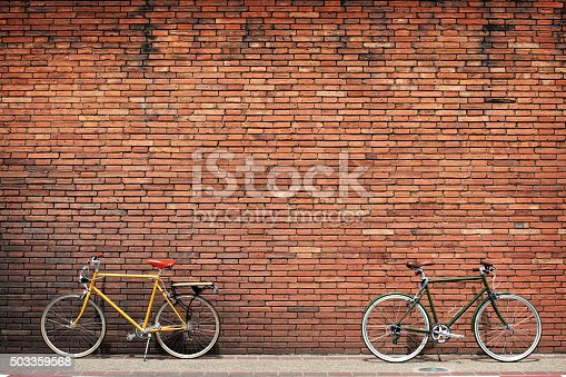 Retro bicycle on roadside with vintage brick wall background