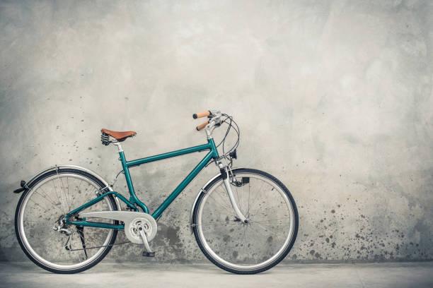 Vélo rétro avec selle en cuir brun âgé de circa 90 s avant fond de mur en béton. Photo filtrée Vintage style ancien - Photo