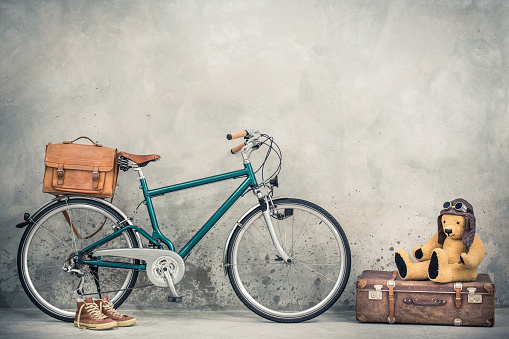 Retro bicycle with leather mailman's bag, old sneakers and Teddy Bear toy in leather aviator's hat and goggles sitting on aged classic travel suitcase front concrete wall. Vintage style filtered photo