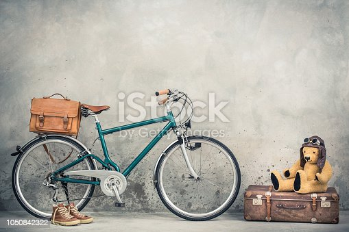 istock Retro bicycle with leather mailman's bag, old sneakers and Teddy Bear toy in leather aviator's hat and goggles sitting on aged classic travel suitcase front concrete wall. Vintage style filtered photo 1050842322