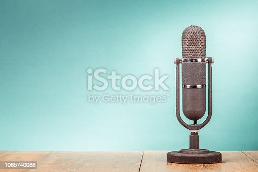 istock Retro big microphone from 50s on table front gradient mint green background. Vintage old style filtered photo 1065740088