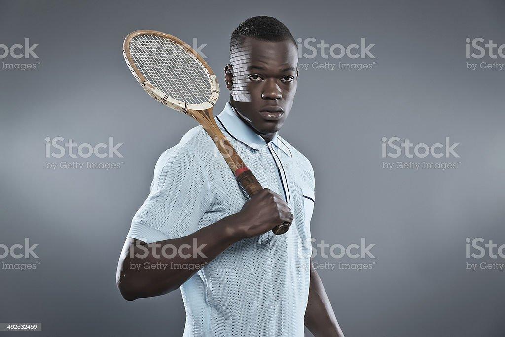 Retro black african tennis player wearing blue shirt. royalty-free stock photo