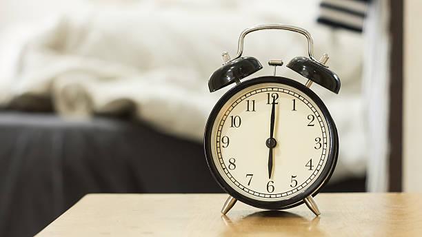 Retro black alarm clock show 6 o'clock in the morning stock photo