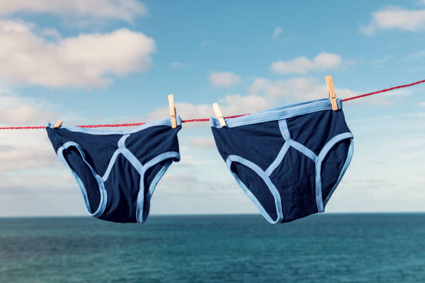 retro blue y-fronts on a washing line overlooking the sea. - washing line stock photos and pictures