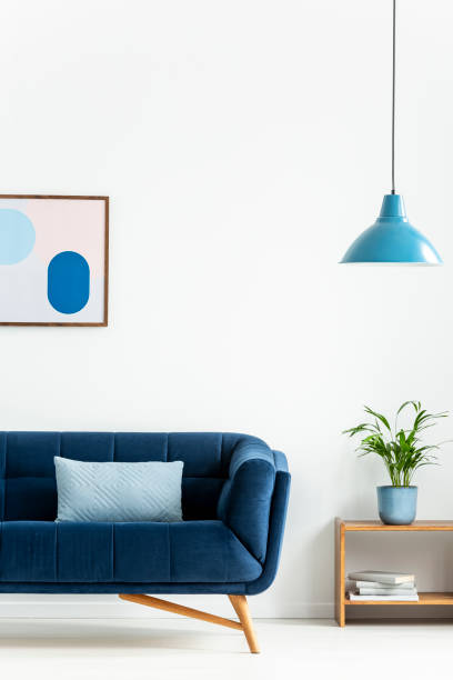 Retro bowl pendant light and a baby blue cushion on a dark, elegant sofa in a simple living room interior with white walls. Real photo. Retro bowl pendant light and a baby blue cushion on a dark, elegant sofa in a simple living room interior with white walls. Real photo. amulet stock pictures, royalty-free photos & images