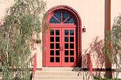 a retro building with bright red arched door entrance and steps