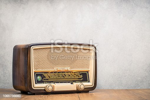 istock Retro broadcast table radio receiver with green eye light, studio microphone circa 1950 on wooden desk front concrete wall background. Listen music concept. Vintage instagram old style filtered photo 1065736660