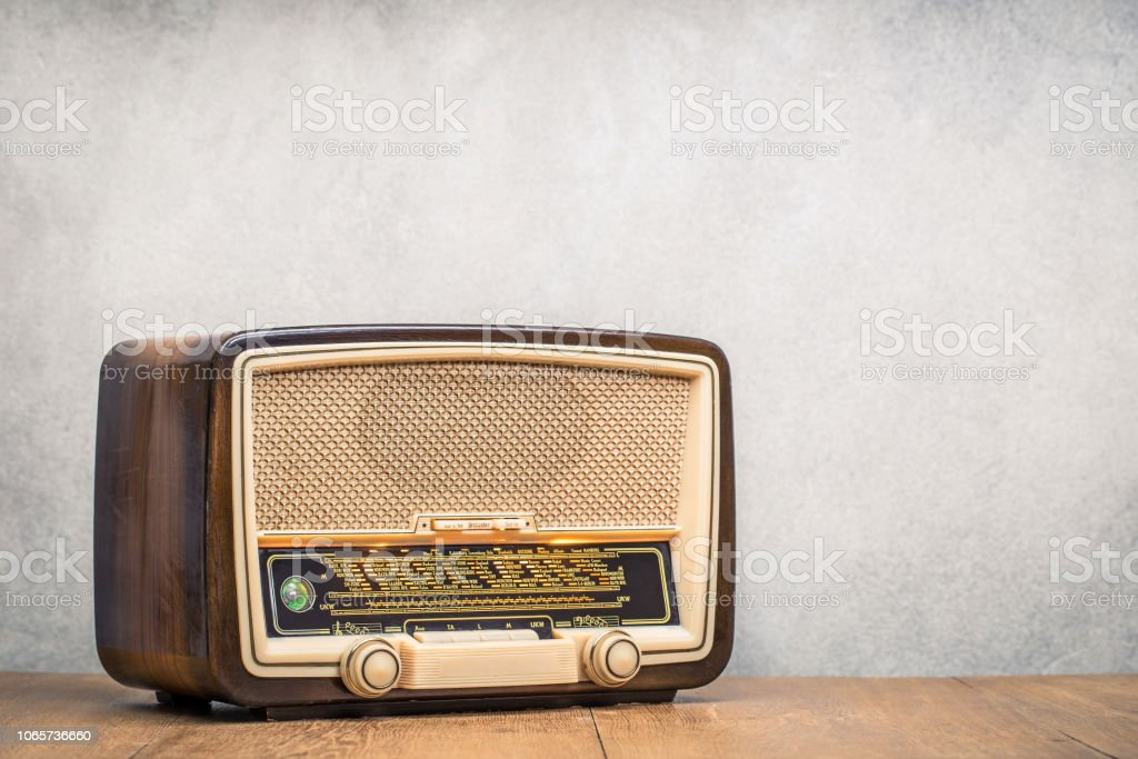 Retro broadcast table radio receiver with green eye light, studio microphone circa 1950 on wooden desk front concrete wall background. Listen music concept. Vintage instagram old style filtered photo stock photo