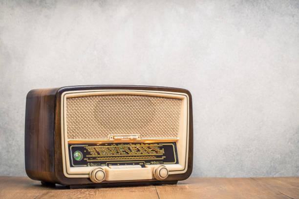 retro uitgezonden tabel radio-ontvanger met groene ogen licht, studio microfoon circa 1950 op houten bureau front betonnen muur achtergrond. luister muziek concept. vintage instagram oude stijl gefilterde foto - archiefbeelden stockfoto's en -beelden