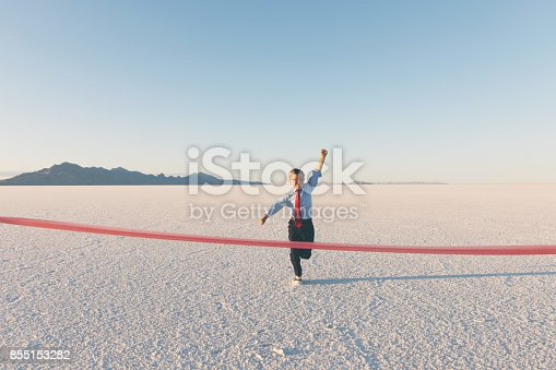 A young business boy dressed in business attire raises his fist while running to the finish line tape. He is excited the hard work, dedication and positive attitude has carried his business to success in the marketplace. Image take on the Bonneville Salt Flats in Utah, USA.