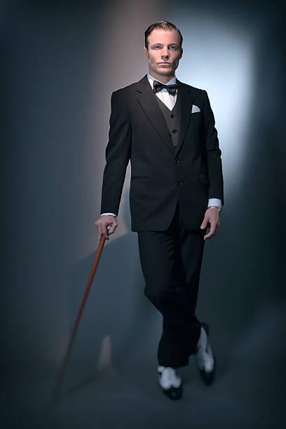 retro business-mode mann mit schwarzen anzug und fliege. - 20er jahre stock-fotos und bilder