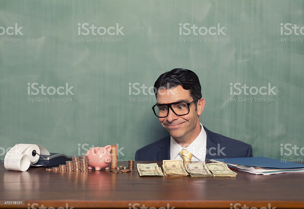 Retro Businessman Counts His Piggy Bank Savings stock photo