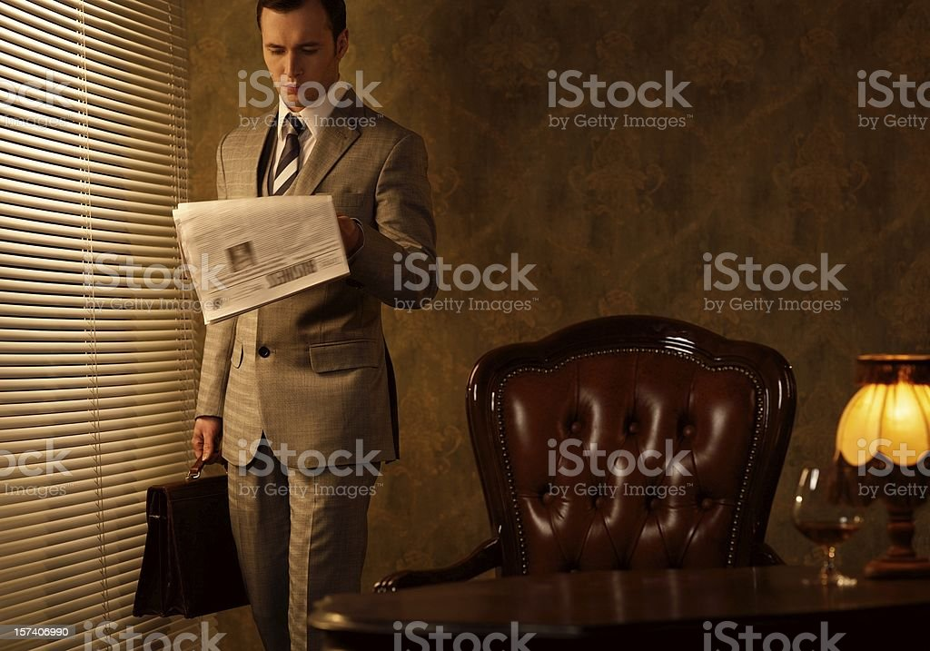 Retro businessman reading newspaper stock photo