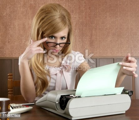 istock Retro businesswoman using typewriter at desk 119832869