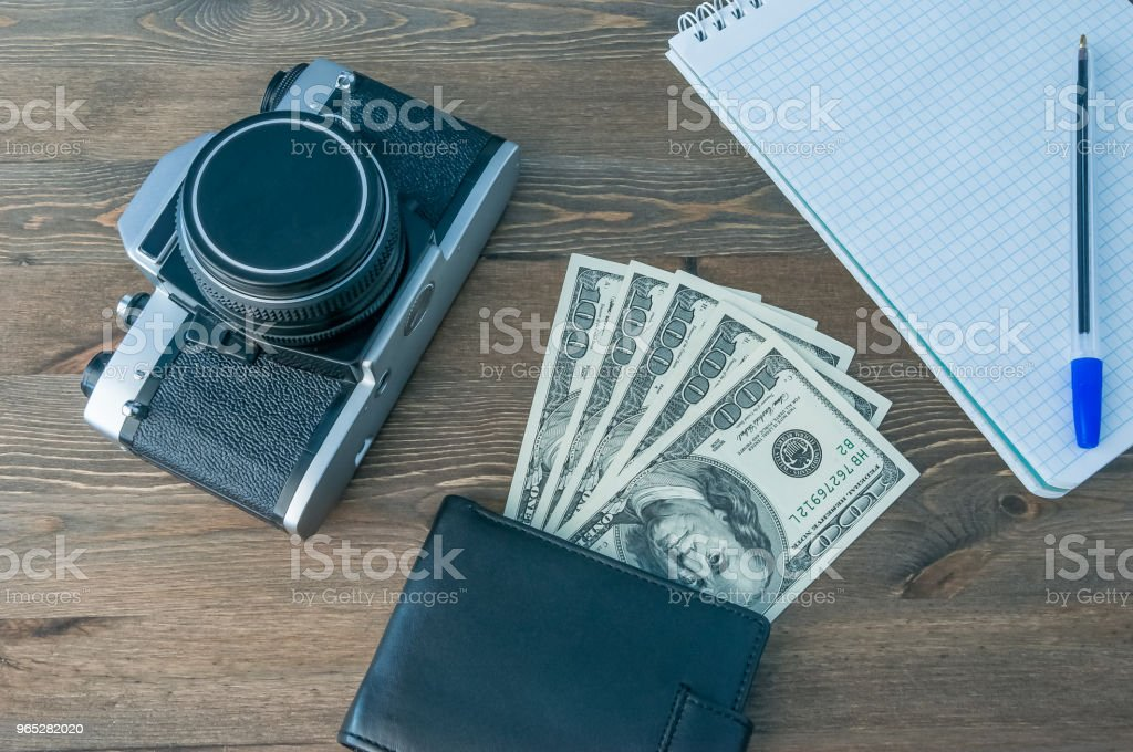A retro camera, a purse with money and a notebook with a pen on a wooden table. royalty-free stock photo