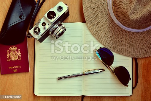 istock Retro camera, hat, passport notebook and pen, all of them on a  wooden table - travel concept 1142897382