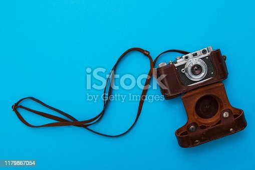 Retro camera in leather case on blue background