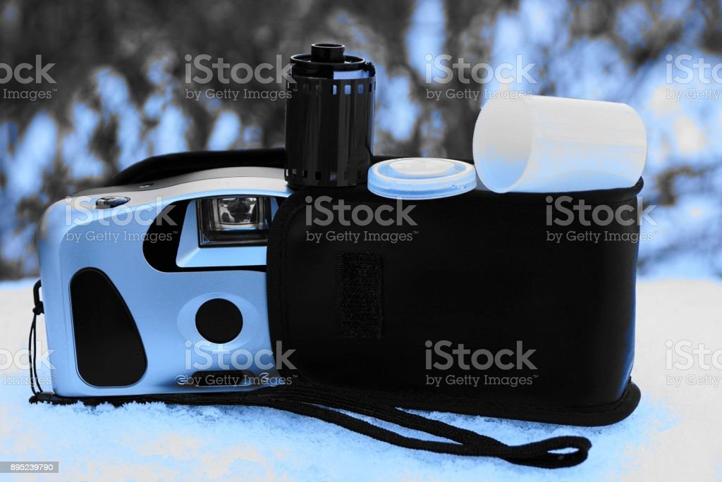 A retro camera with a cover and a film on a snowdrift on the street stock photo