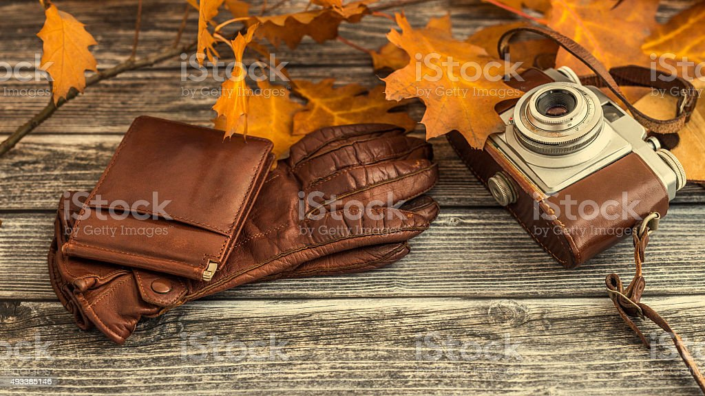 Retro camera with leather case and brown colored gloves stock photo