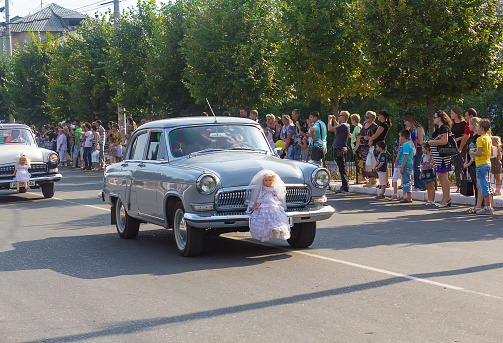 Makeevka, Ukraine - August 25, 2012: Retro cars depicting a wedding procession in the parade during the celebration of the city day