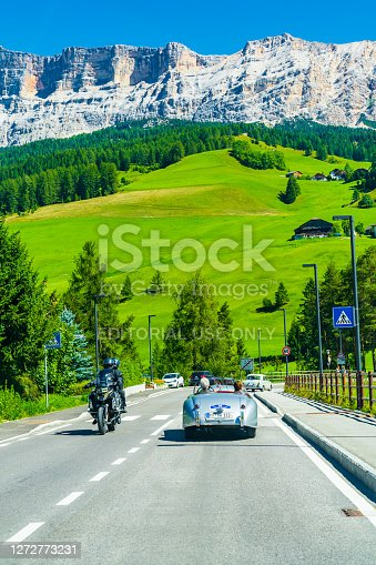 Seniors driving luxurious retro cars in Italian alps, surrounded by meadows and pine forests.