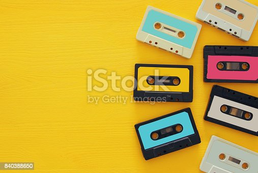 istock Retro cassette tape collection over yellow wooden table. top view. copy space 840388650
