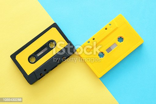 istock Retro cassette tape over yellow and blue double colorful background. top view. copy space. 1055430288