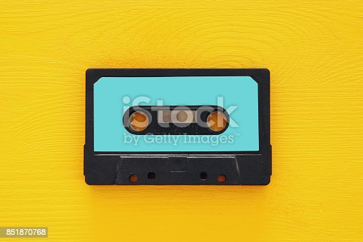 istock Retro cassette tape over yellow wooden table. top view. copy space 851870768