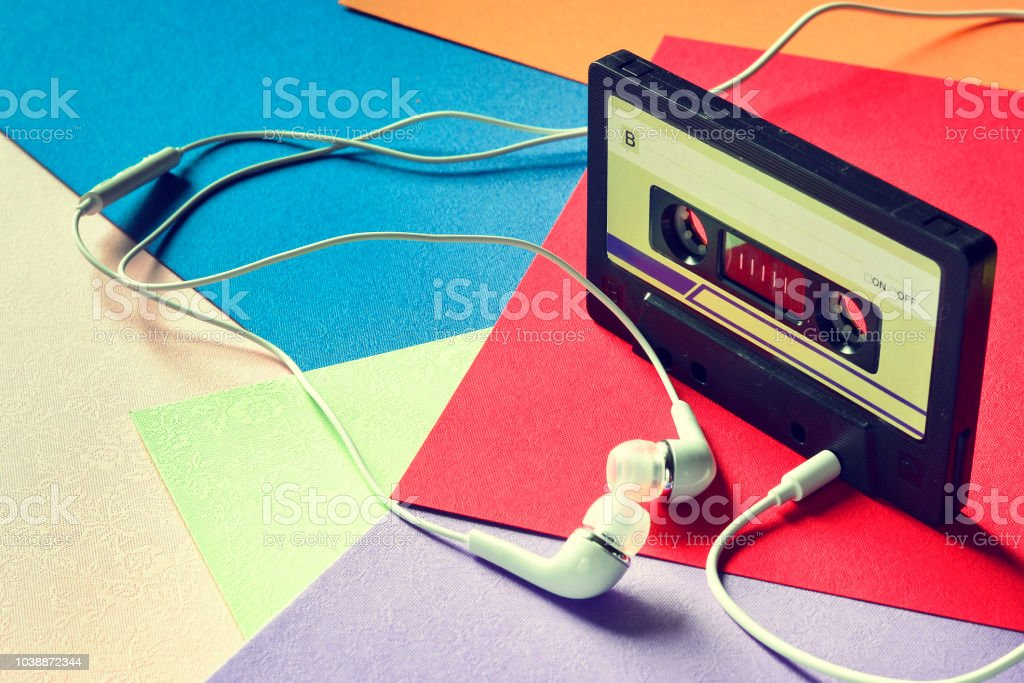 Retro cassette tape rubber with earphones on a colored background – zdjęcie