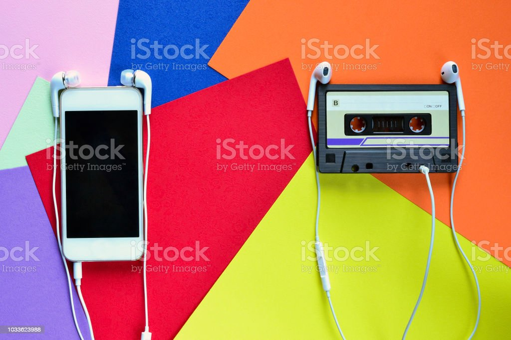 Retro cassette tape rubber with headphones and smartphone on a Colored background – zdjęcie