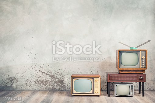 91138159 istock photo Retro cathode ray tube (CRT) monochrome television sets and classic wooden TV stand with outdated amplifier front concrete wall background. Broadcasting, news concept. Vintage old style filtered photo 1222117275