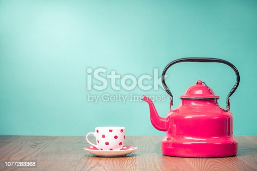 istock Retro classic red kettle and cup of tea with polka dots on oak wooden table in front aquamarine wall background. Vintage old style filtered photo 1077283368