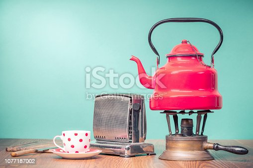 istock Retro classic red kettle on brass gas stove, a cup of tea, outdated bread toaster, kitchen board and vintage knife on oak wooden table in front mint green background. Old style filtered photo 1077187002