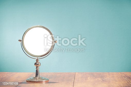 istock Retro classic silver colored round shape makeup mirror frame from circa 50s on aged oak wooden table front mint blue wall background. Nostalgic accessory. Vintage style filtered photo 1224702103