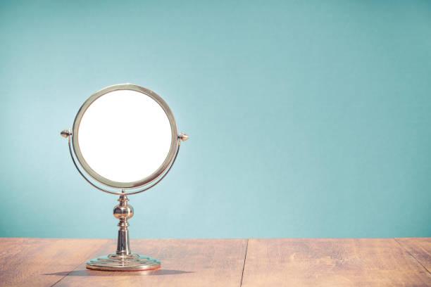 Retro klassische silberfarbene runde Form Make-up Spiegelrahmen aus ca. 50er Jahren auf alten Eichenholz Tisch vorne Mint blau Wandhintergrund. Nostalgisches Accessoire. Vintage-Stil gefiltertfoto – Foto