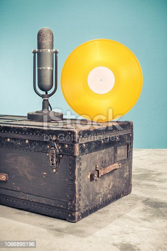 1065736660 istock photo Retro classic studio microphone from 50s and gold vinyl disc record circa 70s on old aged classic travel trunk luggage with leather handles. Vintage style filtered photo 1066895196