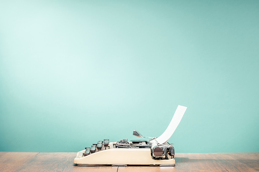 Retro classic typewriter from circa 1950s with sheet of paper on wooden desk front aquamarine wall background. Vintage old style filtered photo
