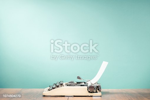 istock Retro classic typewriter from circa 1950s with sheet of paper on wooden desk front aquamarine wall background. Vintage old style filtered photo 1074504270